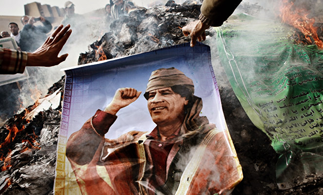 Benghazi residents burn portraits of Muammar Gaddafi, banners with his quotes and his Green Book.