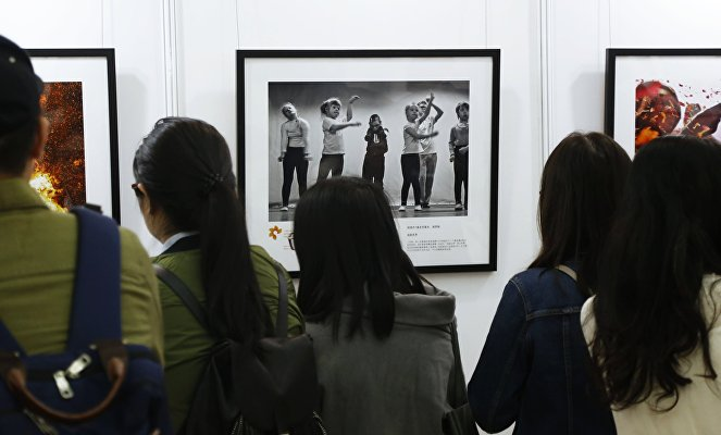 Visitors at the exhibition of winners of Andrei Stenin International Photojournalism Contest in Shanghai.