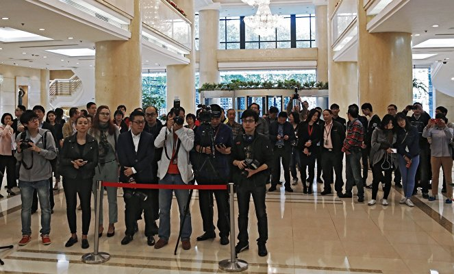 Reporters and visitors at the photo exhibition of the winners of the International Andrei Stenin Photojournalism Contest in Shanghai.