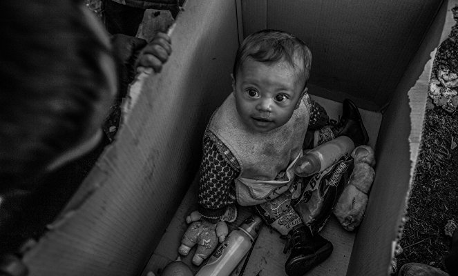 A baby sits in a cardboard box in the Idomeni camp on the Greek-Macedonian border.  For the refugees every border they cross brings them closer to their dream. Their European Dream. The concept of a border is very vague for most refugees. Borders could be anything from a razor wire, to a door of a truck and the Aegean sea.