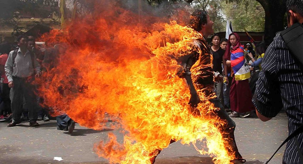 A Tibetan exile runs after setting fire to himself in New Delhi during a protest against Chinese President Hu Jintao's upcoming visit in New Delhi, India, 26 March 2012.