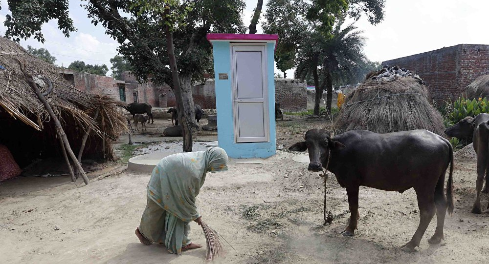 A woman brushes the floor stands next to her new toilet at Katra village in Badaun Uttar Pradesh, India, 31 August 2014.